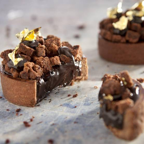 Choco Tartelettes with chocolate filling, brownie pieces and a touch of gold, made by Chef Martin Diez.