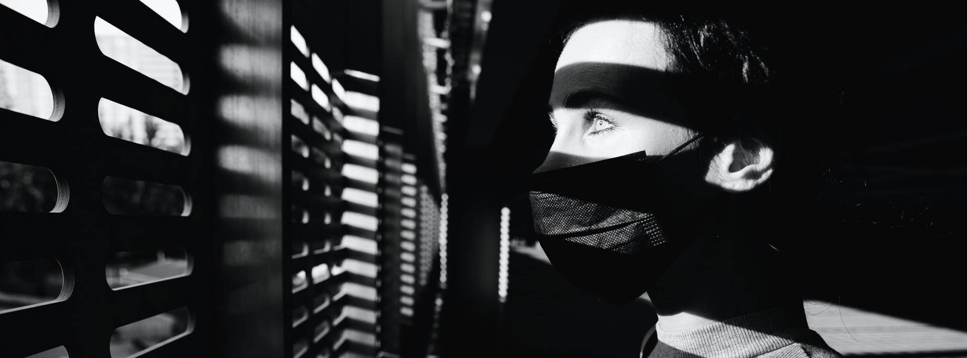 woman looking out blinds while wearing a mask - black and white image