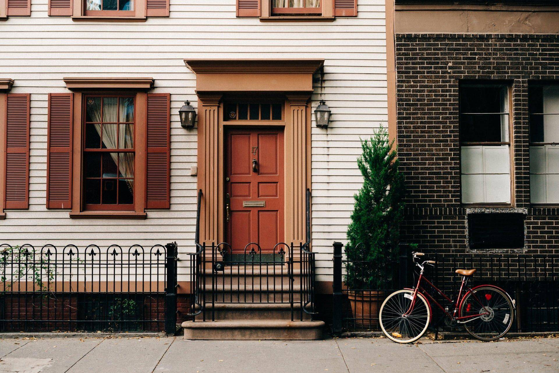 white facade of a city townhome with bicycle parked in front
