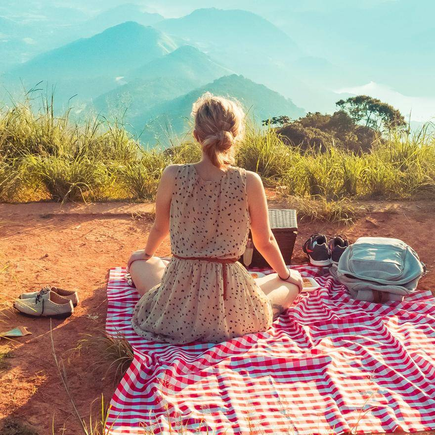 woman sitting on picnic blanket looking at mountains
