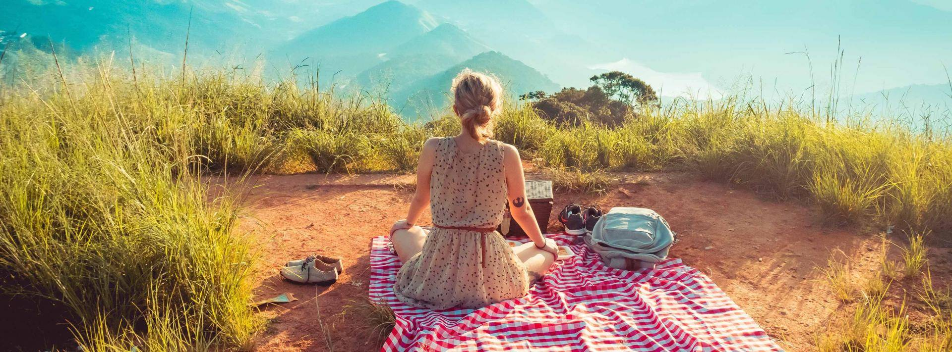 woman sitting on blanket looking at mountains