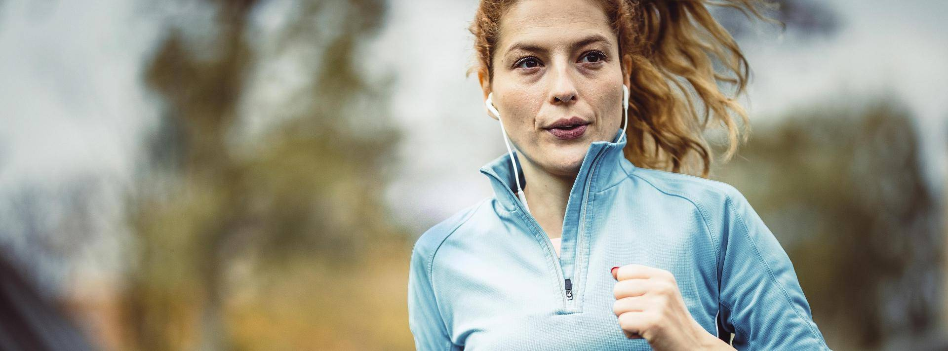 woman running in blue pull-up jacket