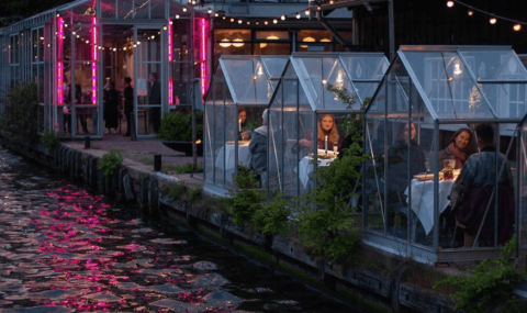 people dining in small glass structures by a river