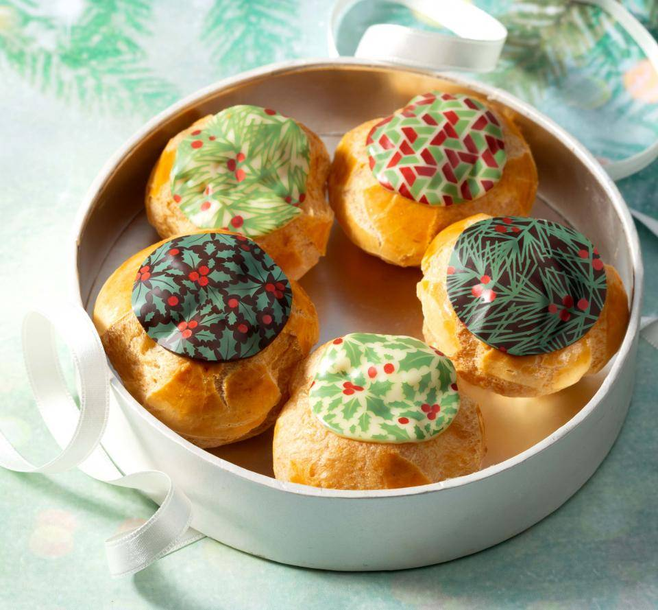 profiteroles decorated with molten chocolate holly leaf christmas designs