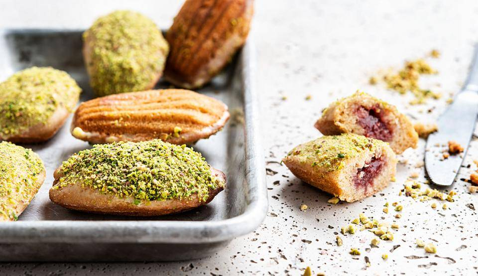 Vegan madeleines, made with raspberry filling and pistachio pieces