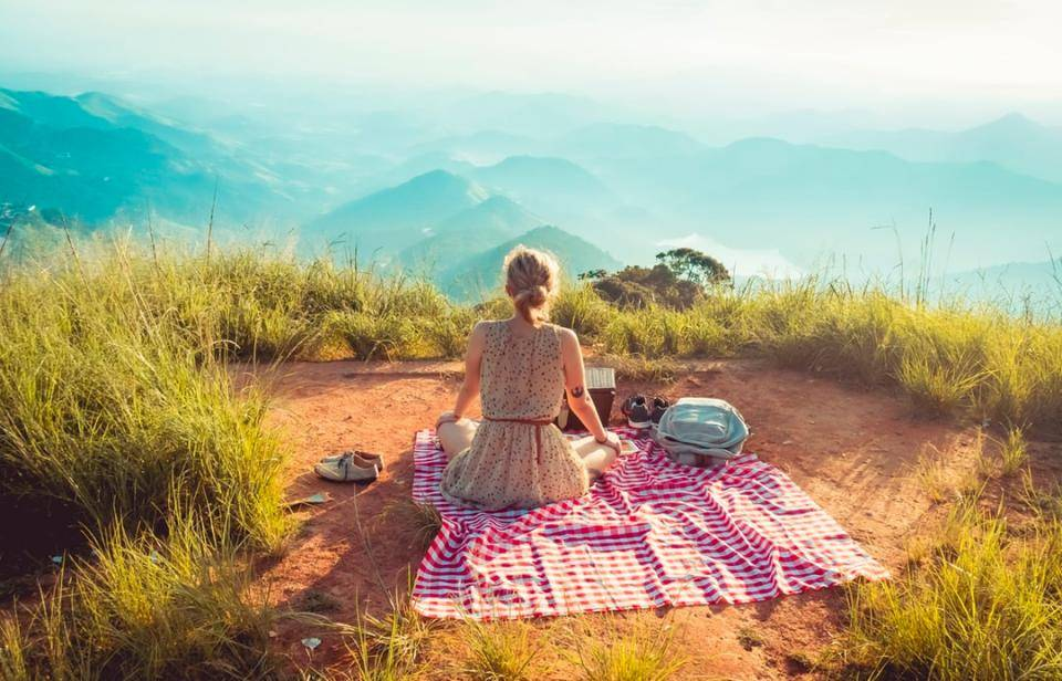 woman sitting on blanket looking out onto horizon