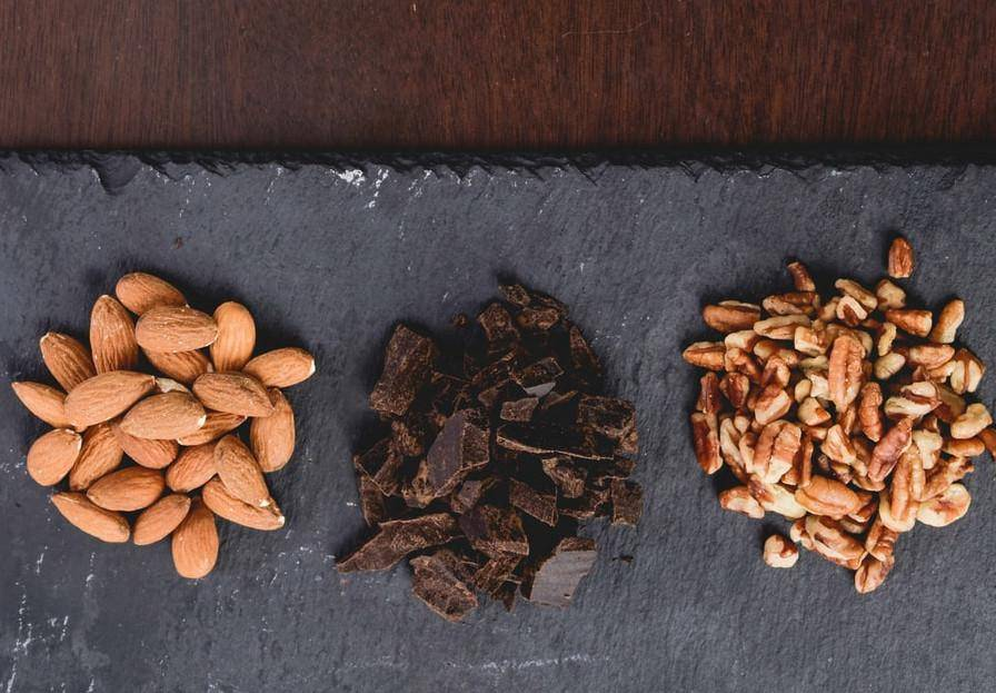 black cutting board with almonds, chocolate, and pecans
