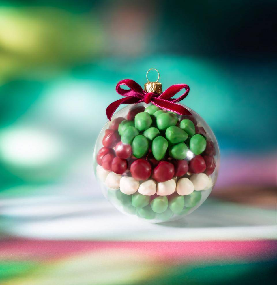 Colored chocolate nibbles in a Christmas Bauble