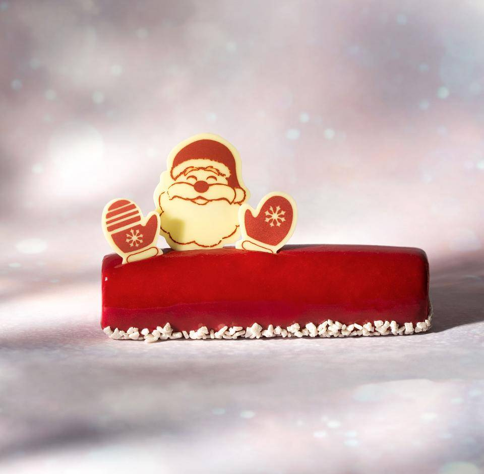 Red Christmas Buche with white chocolate Santa decorations