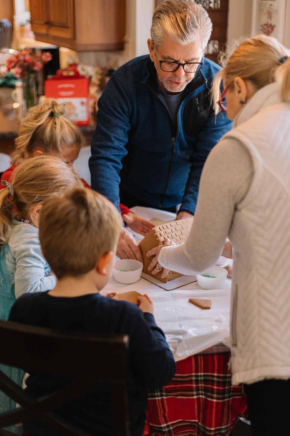 Grandparents creating gingerbread house with grandchildren. Photo by Phillip Goldsberry on Unsplash.