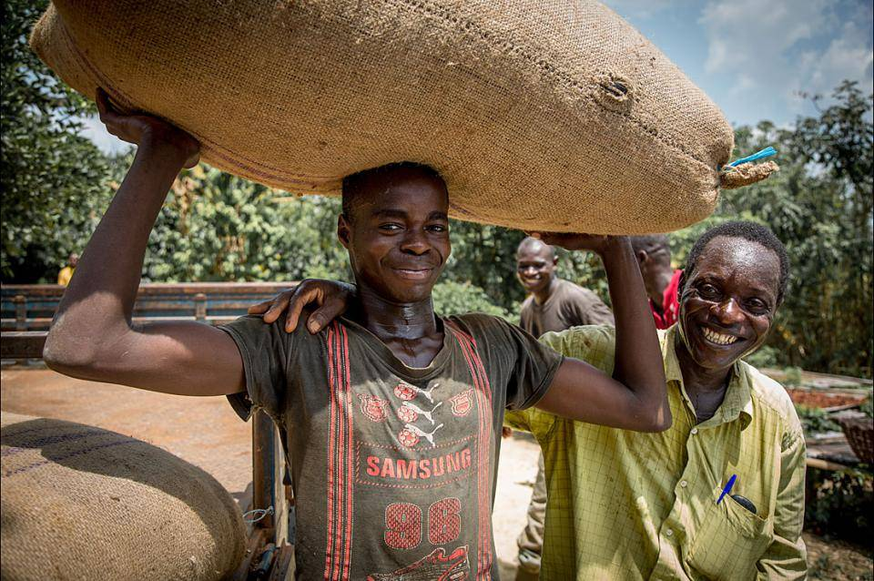 Cocoa farmers with bag of cocoa beans