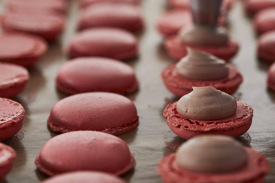 ruby macarons piped with filling