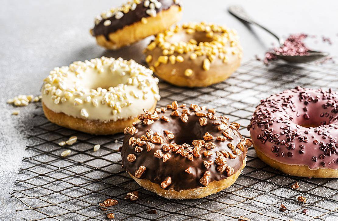 Chocolate-glazed donuts with metallic granella