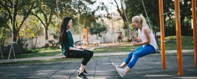 two young women on a swing set