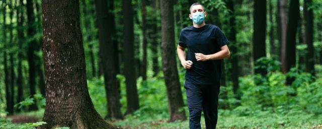man running in woods wearing a mask