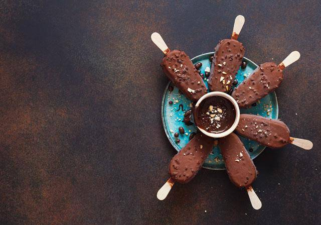 Chocolate covered ice cream bars on a blue plate