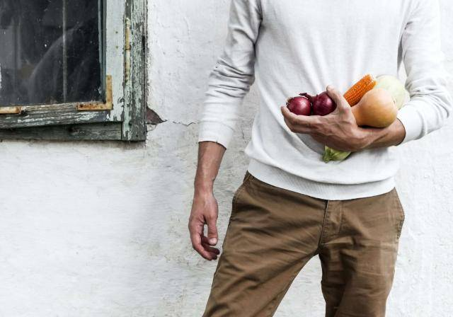 Man standing against white wall holding vegetables