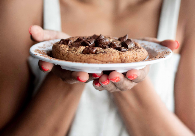 woman holding plate with cookie