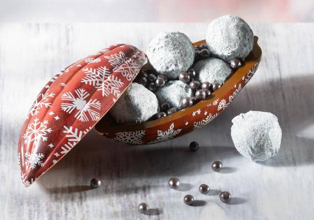 Cocoa pod-shaped chocolate cup, with red print with white snowflakes, willed with silver chocolate truffles and crispearls