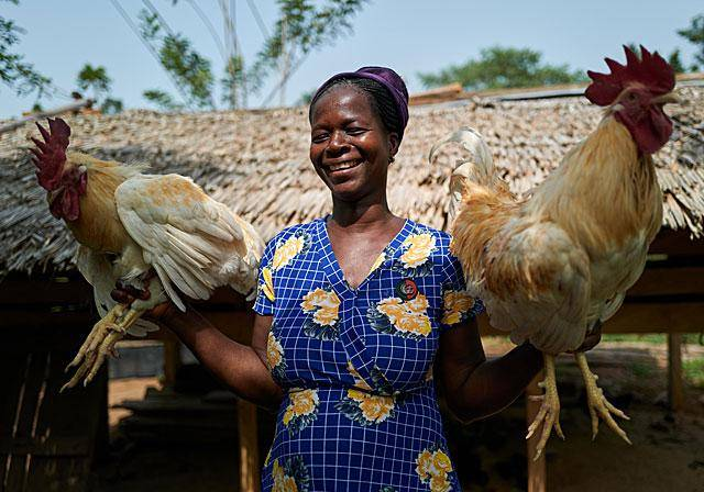 Empower the women Esther holding two roosters from her own farm